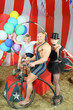happy circus strong man, woman in cylinder and boy on retro bike