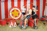 Three funny circus man, woman in cylinder and boy on retro bike
