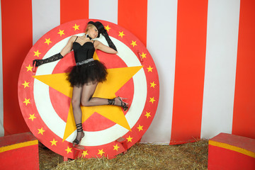 Circus actress in a black top hat stands on circular disc