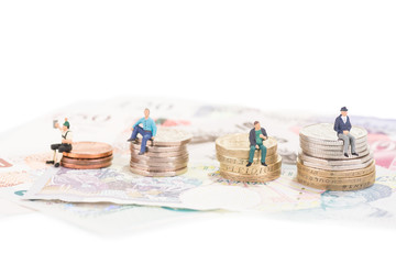 Miniature people sitting on coins close-up