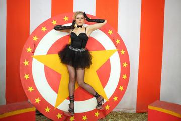 Circus actress in a black  ballet tutu stands on circular disc