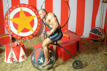 Athlete with grimace riding circus retro bike