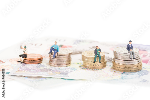 Miniature people sitting on coins close-up - 70565111