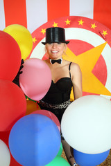Happy circus performer in black hat with balloons in circus tent