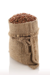 "grade brown rice grain ""devzira"" in a sack on a white background"