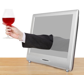 red wine glass in male hand leans out TV screen