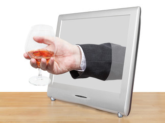 brandy glass in male hand leans out TV screen