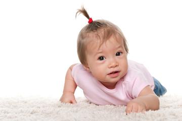 Cute baby girl on the white carpet
