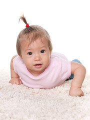 Cute infant girl on the white carpet