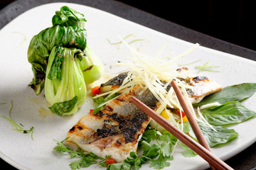 Grilled sea bass fillet with ginger, fresh peppers and pak choy