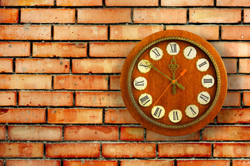 Old vintage clock on background of red brick wall