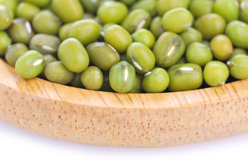 Mung beans on wooden spoon or bowl close up