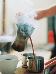 A person holding a coffee perculator and pouring hot coffee into cups.