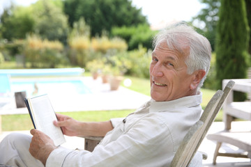 Senior man reading book in pool deck chair