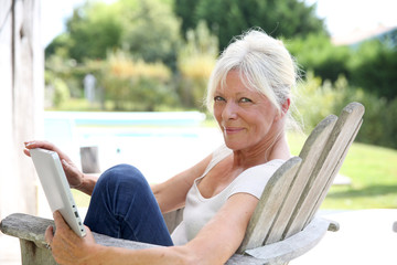 Senior woman reading book by swimming-pool