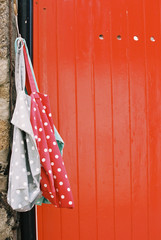 A vividly painted orange door, and two spotted cloth bags hanging from a nail.