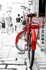 Red bike parked at front of the building.