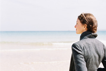 A woman in a grey jacket looking out over a beach and the sea.