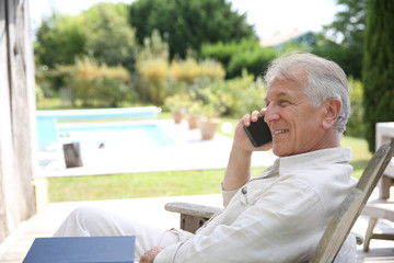 Senior man relaxing in long chair and using telephone
