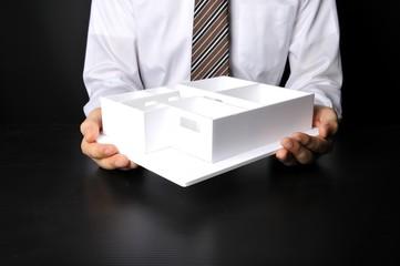 住宅模型を使ってプレゼンしているビジネスマン