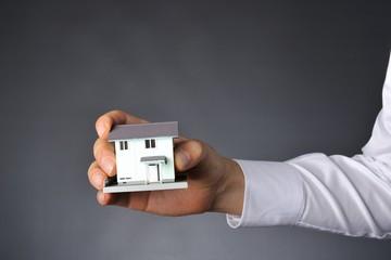 住宅の模型を持つ手