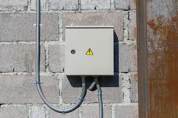 Protective metal box electric meter on the stone wall