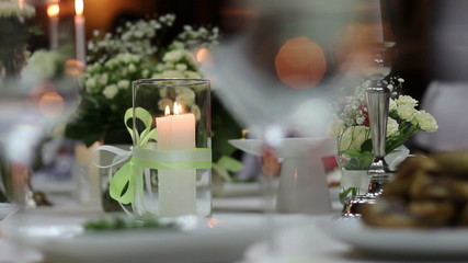 candle in a glass flask on festive table