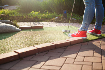 Young woman plays adventure/mini golf in summer evening
