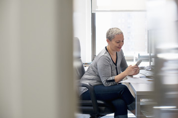 A woman working in an office alone, checking her smart phone.
