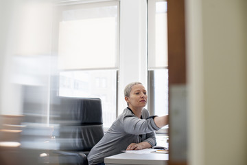 A woman working in an office alone, at her desk leaning forward to look at something.