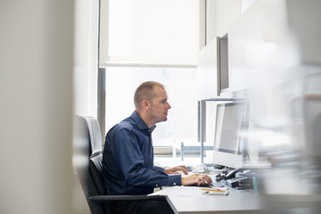 A man working in an office at a desk using a computer mouse. Focusing on a task.