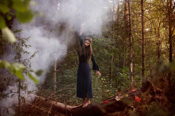 young beautiful witch in autumn forest