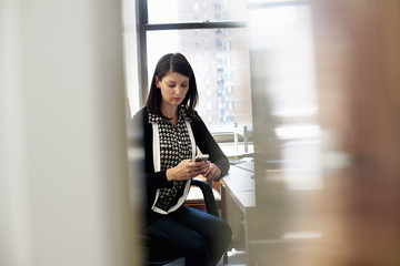 A woman working in an office, sitting checking her smart phone.