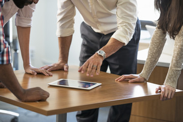 Four people leaning on a table at a meeting