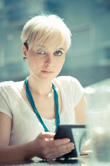 beautiful young blonde short hair hipster woman using tablet