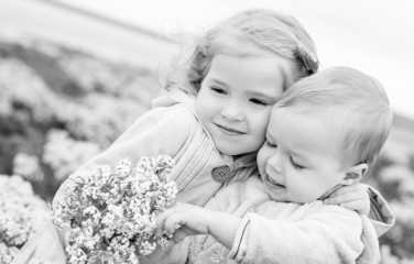 Portrait of the little sister and its toddler brother