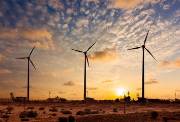 Wind generator turbines sihouettes on sunset