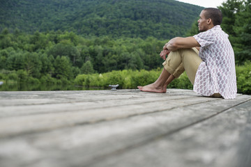 A man sitting on a wooden pier by a lake in summer
