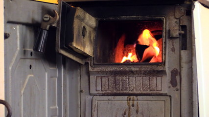 zoom out of burning wood in stove, woman sit in chair and read