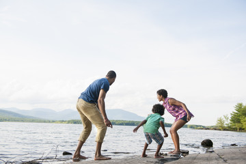 A family, mother, father and son playing on the shores of a lake.