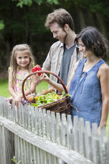 Family standing in a garden with a basket of vegetables.