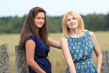 Attractive girls wearing dresses in countryside