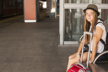 Cute young girl waits for train at the railway station.