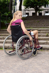 Frau im Rollstuhl vor Treppe als Barriere