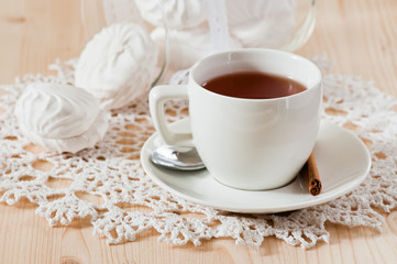 Cup of tea with cinnamon and marshmallows on the lace napkin