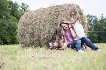 Mother playing outdoors with her daughters.