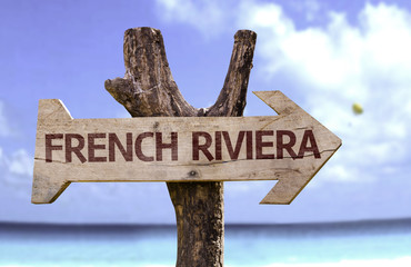 French Riviera wooden sign with a beach on background