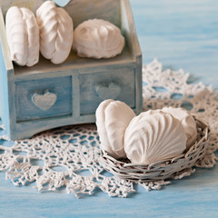 White marshmallows on the lace napkin (blue backgra