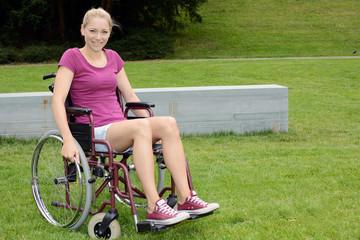 Junge Frau im Rollstuhl auf Wiese