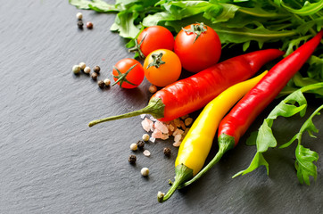 Red and yellow chilis and cherry tomatoes with rucola copy space
